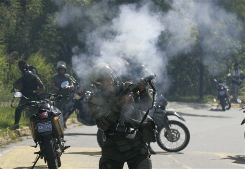 A National Guard fires tear gas at university students during a protest in Caracas, Wednesday, Jan. 14, 2009.  Students protested against a proposed referendum that could allow Venezuela's President Hugo Chavez run for re-election indefinitely.(AP Photo/Fernando Llano)