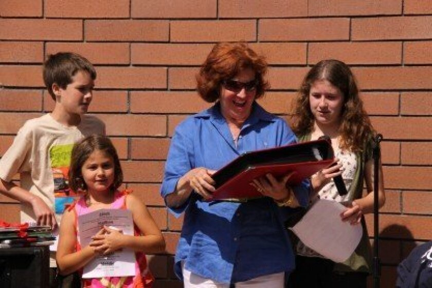 Students Douglas Armstrong, Maddie Ishayik and Alex Delatorre present Suzie Pirtle with a scrapbook filled with notes and photos from former and current students and families.  Photos by Annette Bradbury