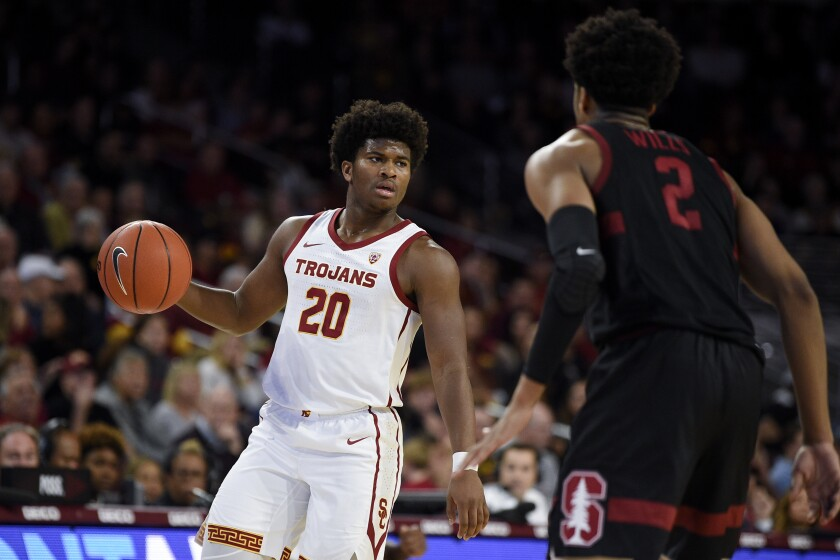 USC guard Ethan Anderson, left, handles the ball in front of Stanford guard Bryce Wills during the first half on Saturday at the Galen Center.