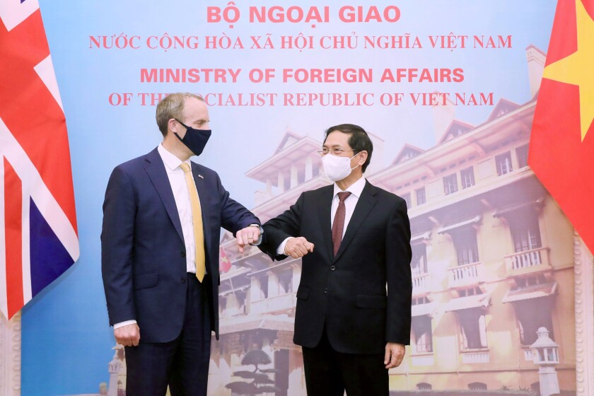 Britain's Foreign Secretary Dominic Raab, left, and Vietnamese Foreign Minister Bui Thanh Son greet with an elbow bump in Hanoi, Vietnam, Tuesday, Jun. 22, 2021. The Britain's top diplomat is on a three-nation visit in Southeast Asia to promote closer ties and trade with the region following the U.K.'s exit from the European Union. (Bui Lam Khanh/VNA via AP)