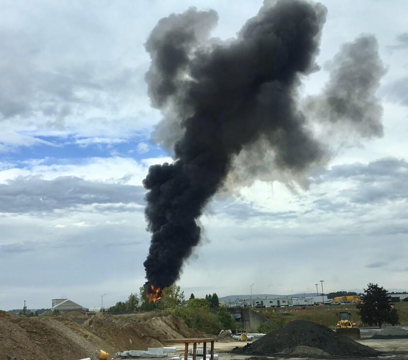 Smoke rises after a World War II-era bomber crashed Oct. 2 outside Bradley International Airport north of Hartford, Conn.