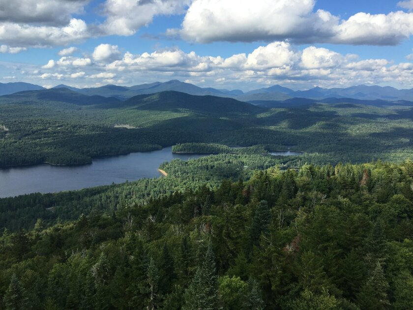 This photo taken on Saturday, Aug. 6, 2016, shows Huntington Wildlife Forest from the top of Goodnow Mountain in New York's Andirondack Mountains, in the center of the 15,000-acre research forest owned by the state College of Environmental Science and Forestry. The nonprofit A2A Collaborative in Lansdowne, Ontario, is planning a hiking trail from here to Algonquin Provincial Park following the general route taken by a radio-collared moose released by wildlife workers here in 1998. The 400-mile A2A Trail, still in early planning stages, is intended to promote protection of the migration corridor used by moose and other wildlife, as well as boost tourist business in villages along the way. (AP Photo/Mary Esch)