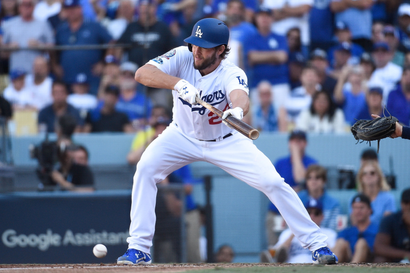 Dodgers pitcher Clayton Kershaw bunts during a playoff game against the Brewers.
