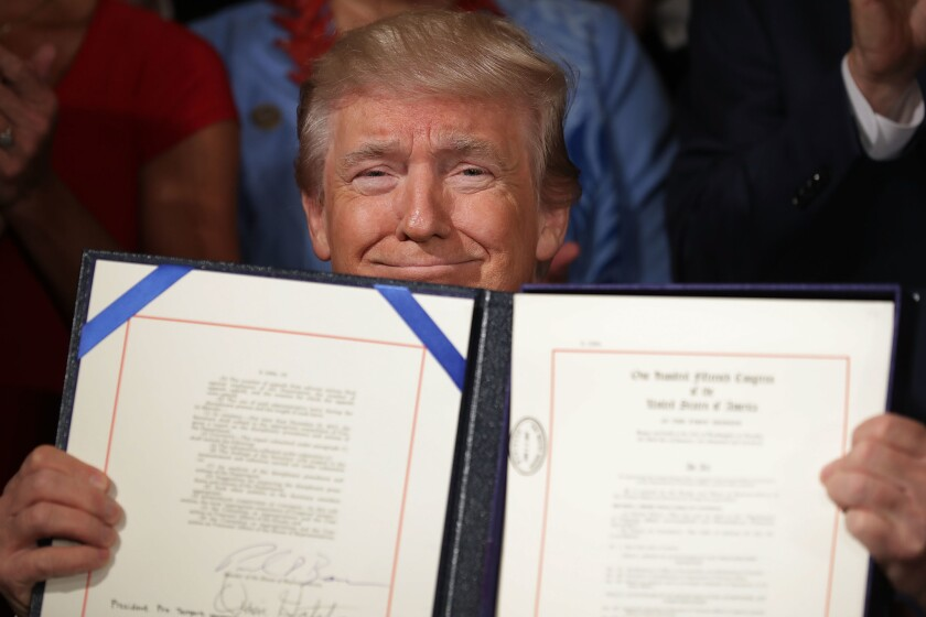 President Trump smiles while holding an open certificate holder with a just-signed bill