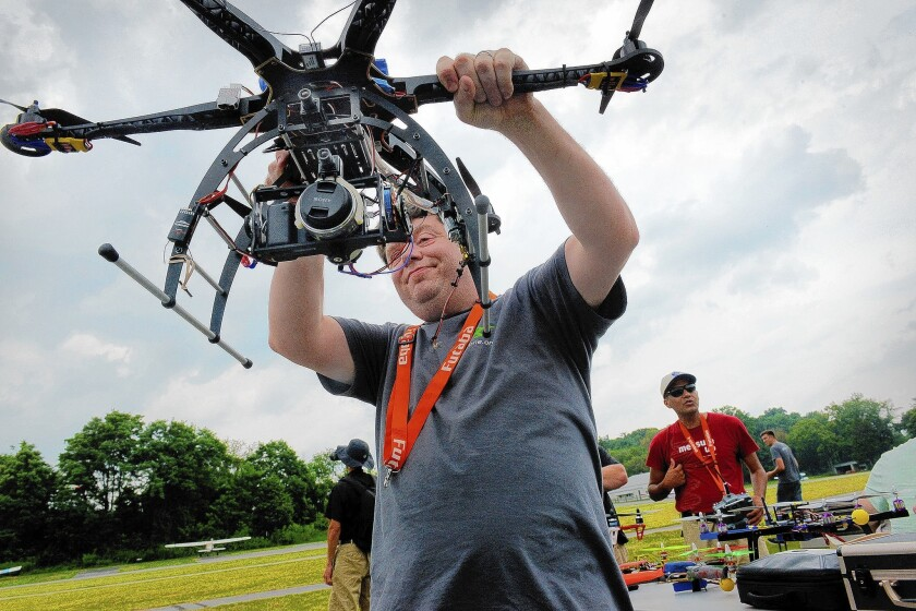 The FAA is weighing a request by seven Hollywood firms to use drones. Above, Terry Kilby inspects a drone before launching it at a gathering of enthusiasts last year in Laytonsville, Md.