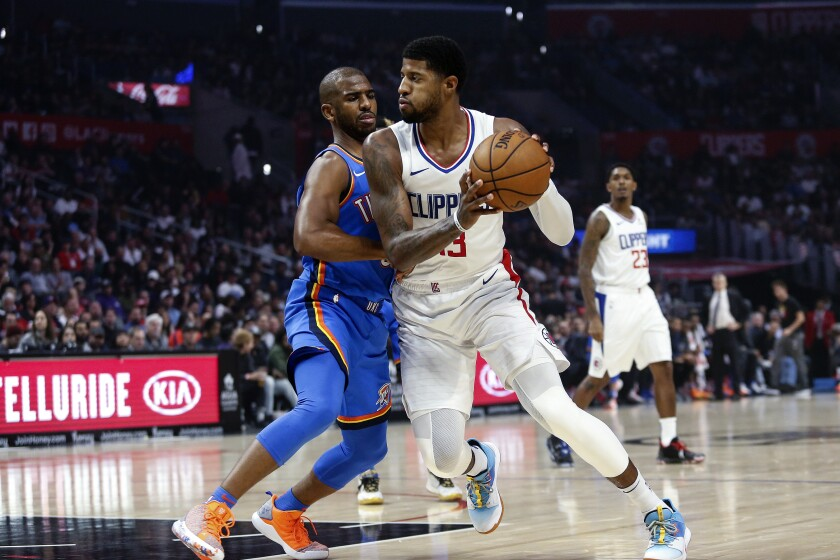 Clippers forward Paul George (13) works against Thunder guard Chris Paul (3) during the first half of a game Nov. 18 at Staples Center.