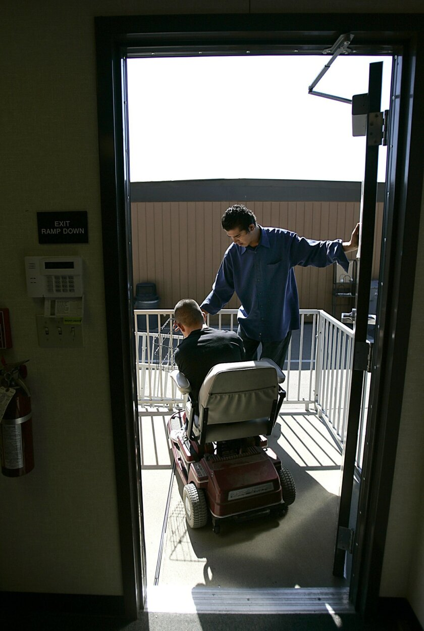 """Eric Noriega (right) helped Horus Ocampo get through a door at Palomar College. Ocampo has had to depend on others to get around. """"Even with all the challenges he has, he's the most positive person,"""" said Ocampo's adoptive mother, Flo Williams. """"He never complains about anything — except when his wheelchair was stolen. That was horrible."""" (John Gastaldo / Union-Tribune)"""