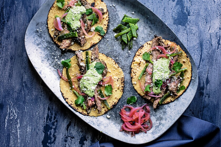 Carne asada made from skirt steak is served with Mexican pickled red onions, a spicy avocado crema and roasted poblano.