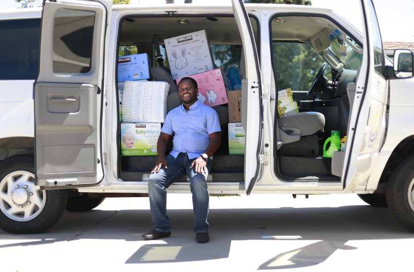 Womaniala Gerald is the CEO of Echoes of Faith, a nonprofit helping local refugees in City Heights during COVID-19 by helping them file for unemployment, delivering food, and translating important COVID-19 information from the government. He is shown here in a van he uses to deliver donated goods.