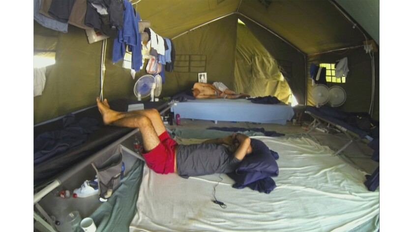 """A still image from the documentary 'Chasing Asylum,"""" shows men in tents in the detention center on Nauru Island."""