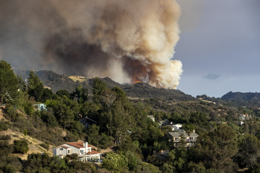 The Palisades wildfire burns out of control in rugged terrain near homes.