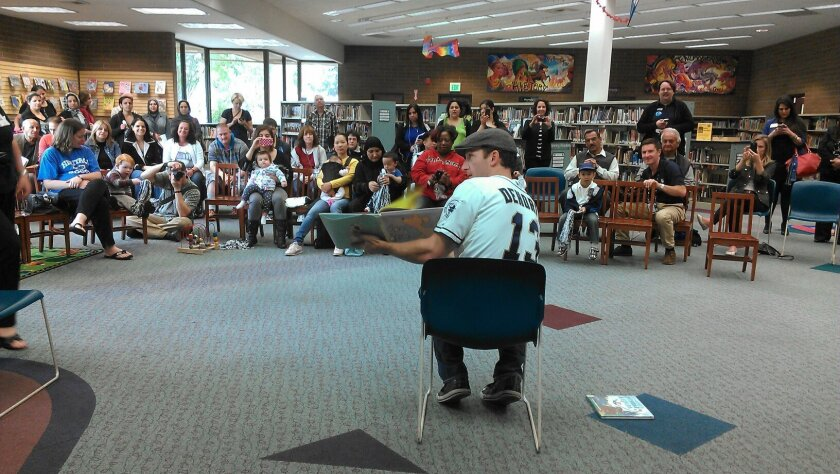 San Diego Padres outfielder Chris Denorfia reads to the crowd on Tuesday morning at the El Cajon Branch Library