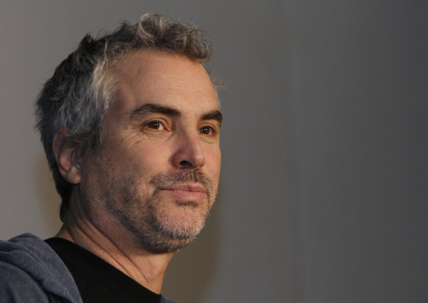 """FILE - In this Oct. 16, 2013 file photo, Mexican filmmaker Alfonso Cuaron poses for photographers during a press conference promoting his film """"Gravity"""" in Mexico City. Despite feeble cries of """"Viva Mexico!"""" by some politicians and celebrities for the best-director nomination of Cuaron, many here s"""