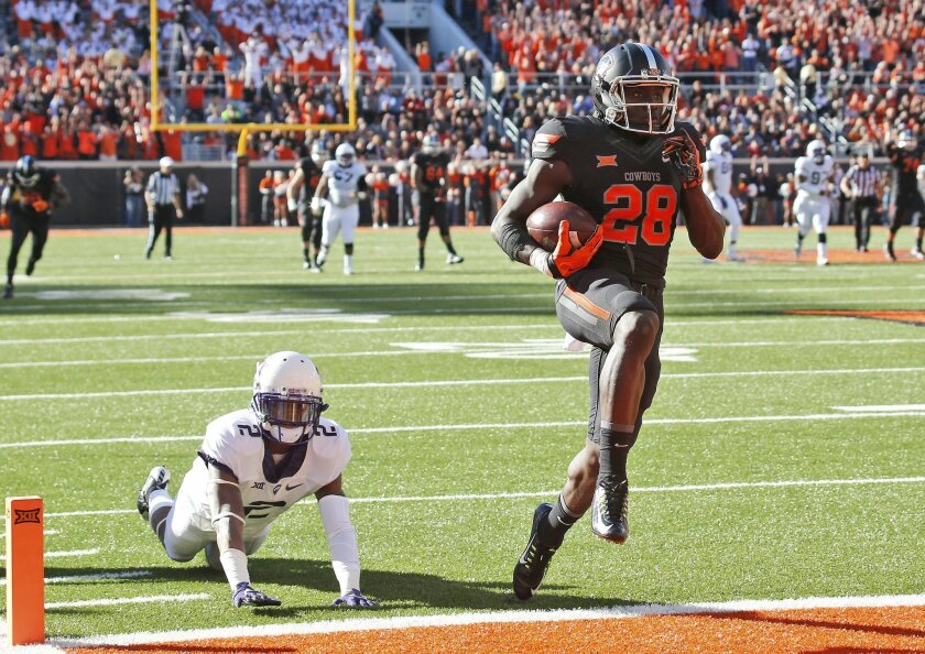 Oklahoma State wide receiver James Washington (28) carries a Mason Rudolph pass into the end zone for a touchdown in front of TCU cornerback Torrance Mosley (2) in the first quarter of an NCAA college football game in Stillwater, Okla., Saturday, Nov. 7, 2015. (AP Photo/Sue Ogrocki)