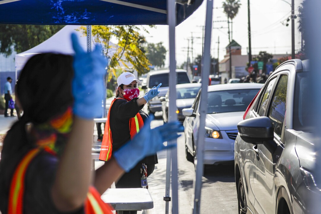 LAUSD cafeteria crew directs cars approaching meal bag distribution stations