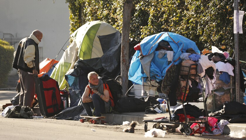 Homeless people outside their tents with their possessions on the street