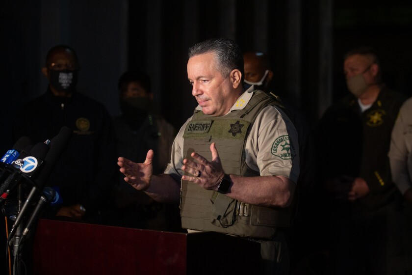 L.A. County Sheriff Alex Villanueva, wearing a bulletproof vest, speaks at a late-night news conference