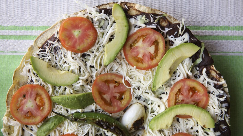 A vegetarian Tlayuda with avocado, tomato, beans, cabbage and cheese - topped with a fried serrano chile and a grilled Mexican green onion, is arranged for a photograph at Antequera de Oaxaca.