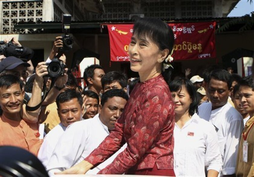 Myanmar's pro-democracy leader Aung San Suu Kyi greets her supporters as she leaves a ceremony to mark the 64th Independence Day at her National League for Democracy party's headquarters in Yangon, Myanmar, Wednesday, Jan. 4, 2012. (AP Photo/Khin Maung Win)
