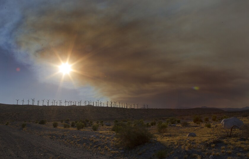 Wind turbines near the 10 freeway in Cabazon are framed by the smoke from the Lake fire