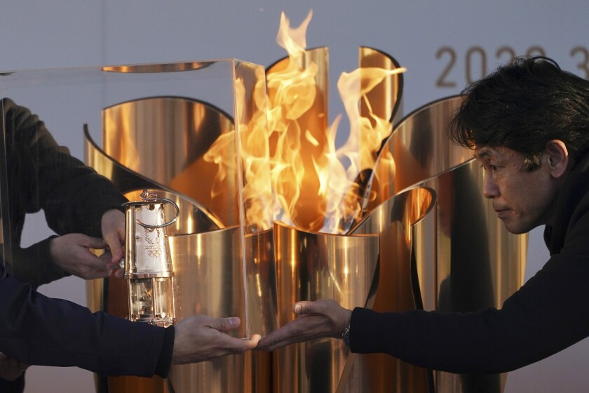 Officials light a lantern from the Olympic flame at the end of a ceremony in Iwaki, northern Japan, on March 25, 2020. Before the Olympics were postponed, Japan looked like it had coronavirus infections contained.