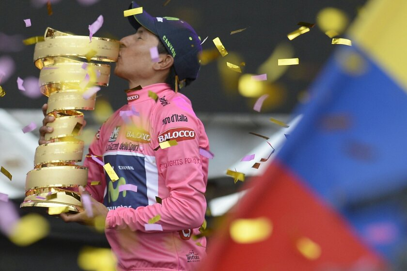 Colombia's Nairo Quintana kisses the trophy after winning the Giro D'italia, Tour of Italy cycling race, from Gemona to Trieste, Sunday, June 1, 2014. Nairo Quintana confirmed himself as cycling's next star by winning the Giro d'Italia on Sunday to follow his runner-up finish in last year's Tour de France. The 24-year-old climbing specialist with the Movistar team won two stages and finished with a 3 minute, 7 second advantage over fellow Colombian Rigoberto Uran for his first Grand Tour victory. Italy's Fabio Aru finished third overall, 4:04 back. (AP Photo/Fabio Ferrari)