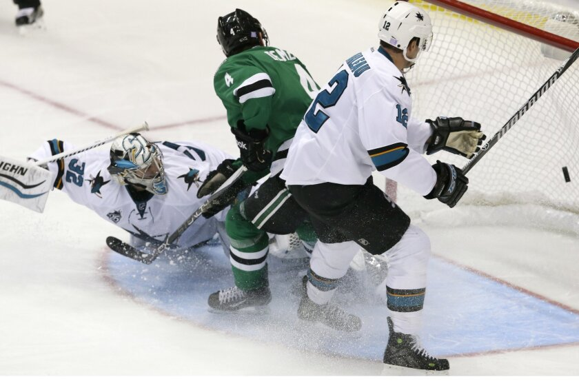 Dallas Stars defenseman Jason Demers (4) scores a goal against San Jose Sharks goalie Alex Stalock (32) and center Patrick Marleau (12) during the second period of an NHL hockey game Saturday, Oct. 31, 2015, in Dallas. (AP Photo/LM Otero)