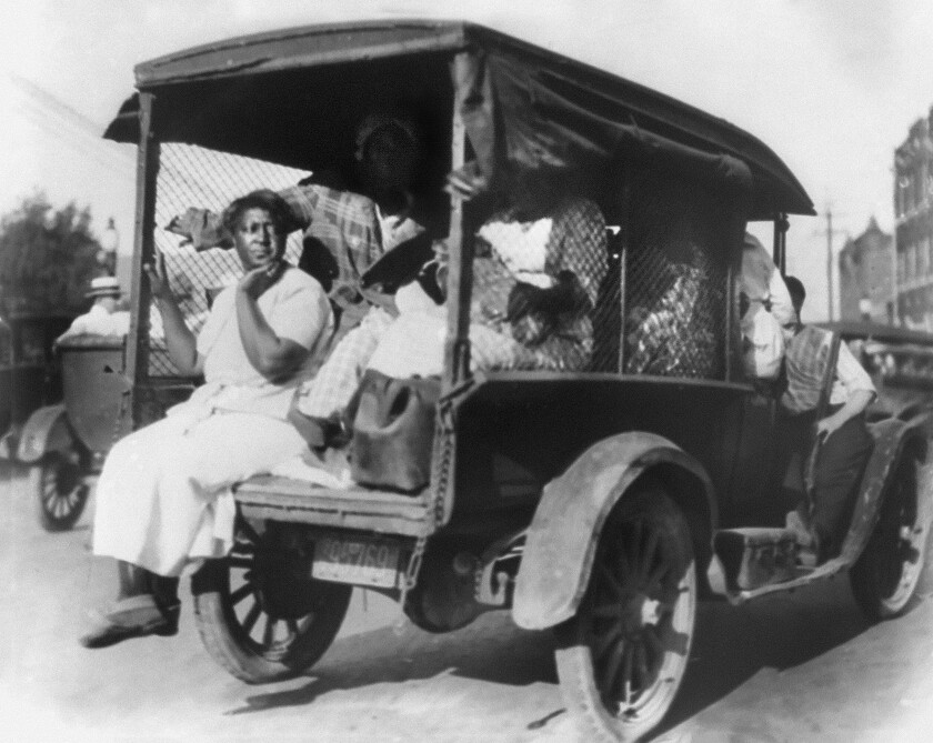 A woman puts a hand to her chin while riding on the back of a truck.