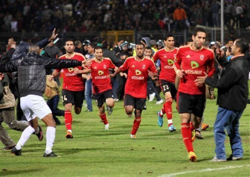 Team players of the Egyptian Al-Ahly club run for safety during clashes following their soccer match against Al-Masry club at the soccer stadium in Port Said, Egypt Wednesday, Feb. 1, 2012. Dozens of Egyptians were killed Wednesday in violence following a soccer match in Port Said, when fans flooded the field seconds after a match against a rival team was over, Egypt's Health ministry said. (AP Photo/Ahmed Hassan)