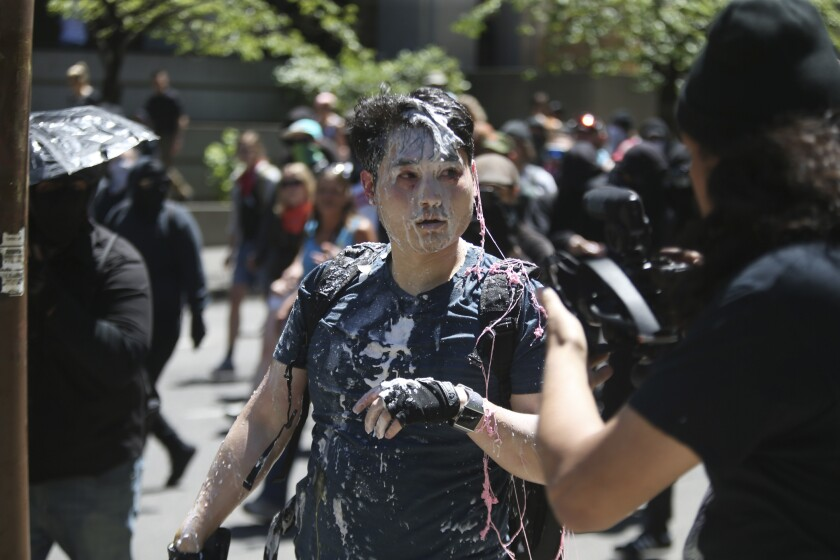 "In this June 29, 2019, photo, Andy Ngo, a conservative writer, is seen after being attacked by a group of left-wing protesters at a demonstration in Portland, Ore. Ngo has filed a lawsuit against purported elements of the nebulous far-left-leaning militant groups collectively known as antifa on Thursday, June 4 2020. Ngo has drawn attention to antifa for years and says he was targeted and suffered brain injuries when he was assaulted while covering protests in Portland a year ago. The suit seeks $900,000 in damages, claiming assault, battery and intentional infliction of emotional distress, and an injunction barring the group from further harassment, accusing Rose City Antifa of ""pattern of racketeering activities"" among other legal claims. (Dave Killen/The Oregonian via AP)"