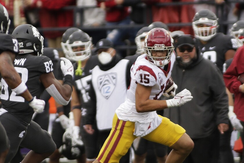 USC wide receiver Drake London runs with the ball while being chased by Washington State linebacker Travion Brown.