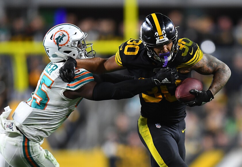 Steelers running back James Conner tries to fend off Dolphins linebacker Jerome Baker on Oct. 28, 2019.