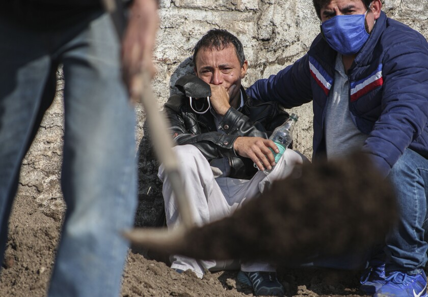 Peruvian migrant Jose Collantes cries as he watches cemetery workers bury his wife Silvia Cano, who died of COVID-19 complications according to Collantes, at a Catholic cemetery in Santiago, Chile, Friday, July 3, 2020. Collantes said he preferred to cremate her in order to take the ashes home with him, but due to bureaucracy had already been waiting two weeks. (AP Photo/Esteban Felix)