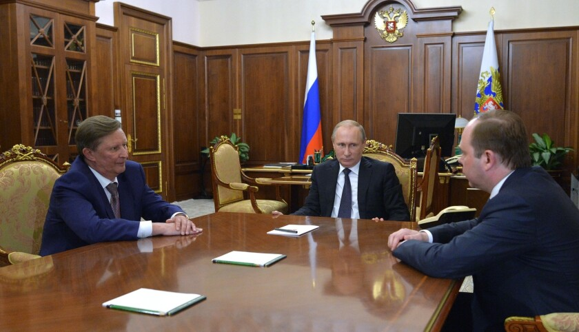 Russian President Vladimir Putin, center, meets with the new chief of the presidential administration, Anton Vayno, right, and the outgoing Kremlin chief of staff, Sergei Ivanov, in the Kremlin on Aug. 12, 2016.