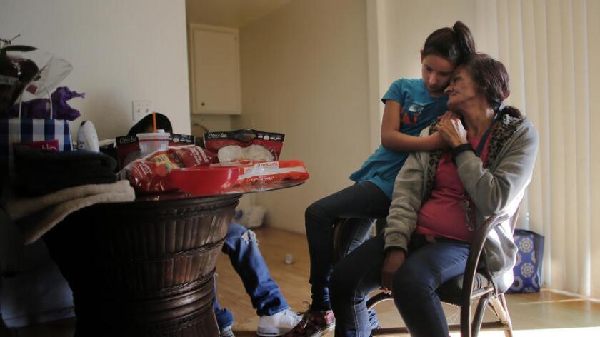 Regina Bejarano consuela a su nieta, Honestie Díaz, de 10 años, en su hogar de San Bernardino (Gina Ferazzi / Los Angeles Times).