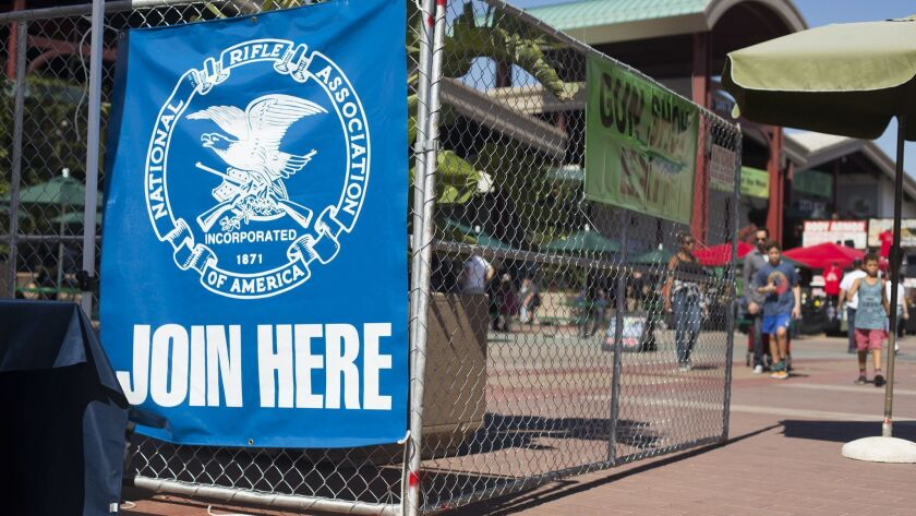 A National Rifle Assn. banner is displayed near the entrance of a Crossroads of the West Gun Show at the OC Fair & Event Center in Costa Mesa in October. Orange County Fair Board members voted Thursday to approve contracts for three more shows this year.