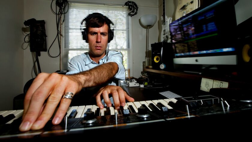 """Composer and musician Nick Thorburn, who wrote the theme music for """"Serial,"""" plays a synthesizer inside his home studio in Los Angeles."""