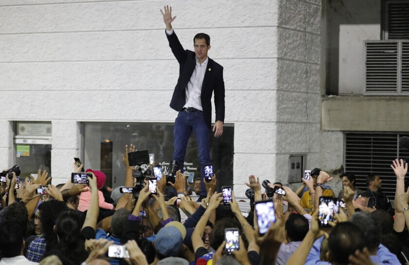 Opposition leader Juan Guaido waves to supporters during a rally at Bolivar Plaza in Chacao, Venezuela, Tuesday, Feb. 11, 2020. Guaido returned home from a tour of nations that back his effort to oust socialist leader Nicolas Maduro. (AP Photo/Ariana Cubillos)