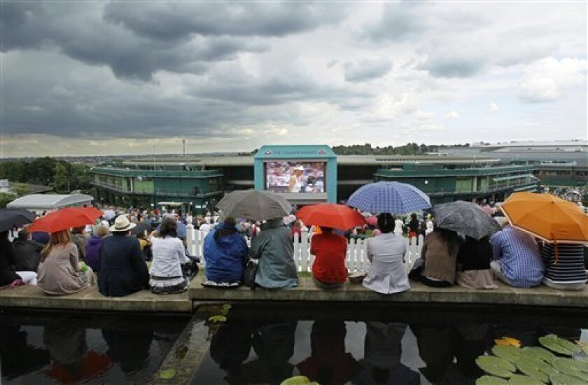 Spectators shelter under umbrellas as they watch the semifinal between Russia's Maria Sharapova and Germany's Sabine Lisicki on the grounds of Wimbledon on a giant screen at the All England Lawn Tennis Championships at Wimbledon, Thursday, June 30, 2011. (AP Photo/Kirsty Wigglesworth)