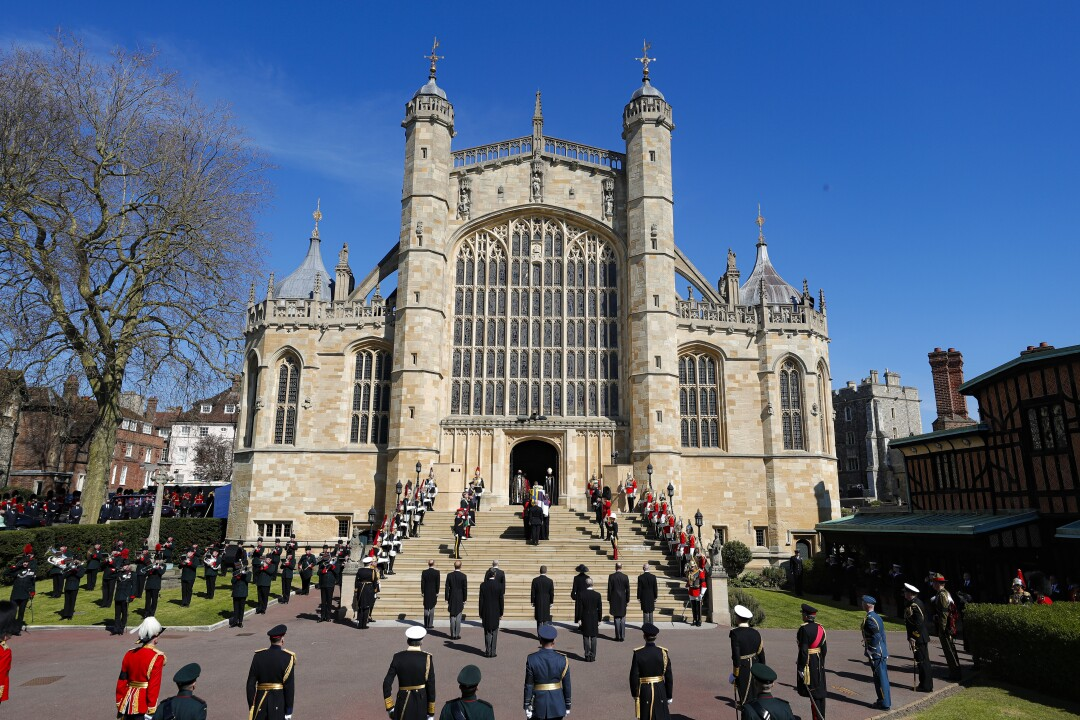 A minute of silence is observed outside St. George's Chapel at Windsor Castle as military and royal family members stand.