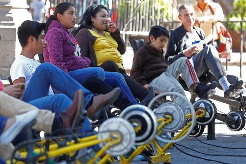 Fotografía del 11 de noviembre de 2017, que muestra a personas montando bicicletas estáticas como parte de las actividades del Sexto Festival Rodante, en el zócalo de Puebla (México). EFE