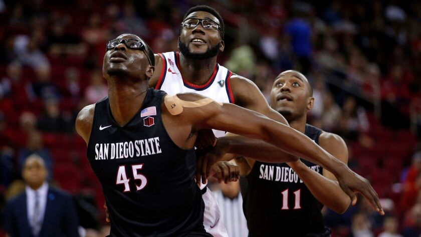 SDSU's Valentine Izundu blocks out Fresno State's Karachi Edo in the second half of the Aztecs' 70-67 win Saturday at the Save Mart Center.