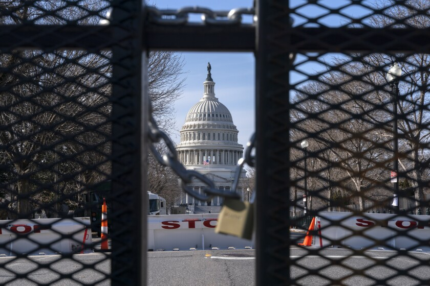 With the U.S. Capitol in the background, a lock on anti-scaling security fencing is seen on Saturday in Washington.