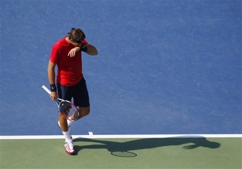 Argentina's Juan Martin Del Potro wipes his face during his match against Ryan Harrison  in the third round of play at the 2012 US Open tennis tournament,  Friday, Aug. 31, 2012, in New York. (AP Photo/Paul Bereswill)