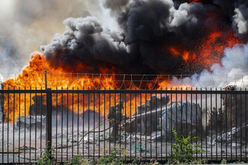 ONTARIO, CA - APRIL 30, 2019: An Ontario firefighter battles huge flames and black smoke while tryin