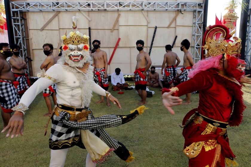 Bailarines disfrazados se preparan para ejecutar una danza tradicional durante un desfile en Bali,