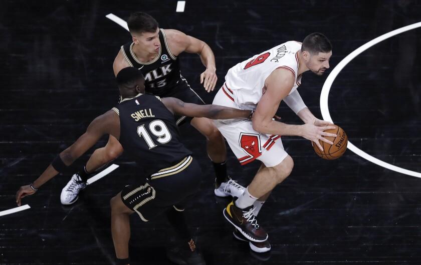 Chicago Bulls' Nikola Vucevic, right, drives the ball away from Atlanta Hawks' Tony Snell (19) and Bogdan Bogdanovic (13) during the second half of an NBA basketball game Friday, April 9, 2021, in Atlanta. (AP Photo/Ben Margot)