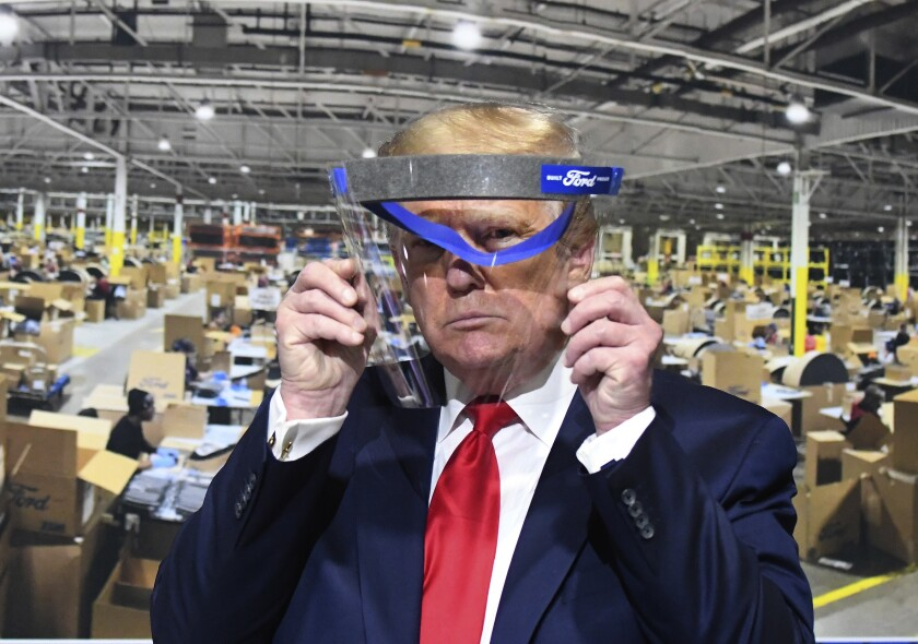 President Trump looks through a face shield while touring a Ford Motor Co. plant in Ypsilanti, Mich., in May.
