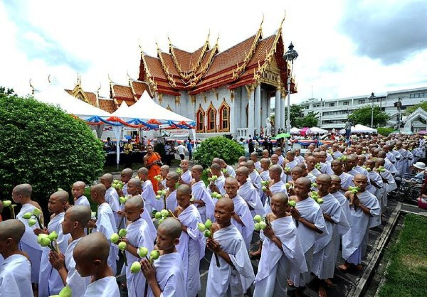 Thai Buddhist novices walk around the Marble Temple, holding lotus flowers and candles, during a ceremony to mark their passage into monkhood in Bangkok, Thailand.