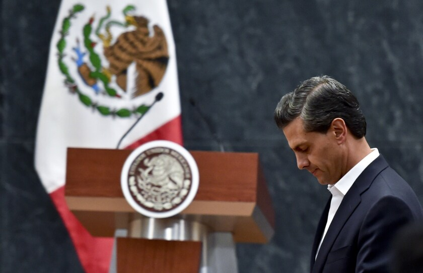 Mexican President Enrique Peña Nieto leaves after delivering a message to the media Wednesday after a meeting with parents of 43 missing students at the Los Pinos presidential palace in Mexico City.